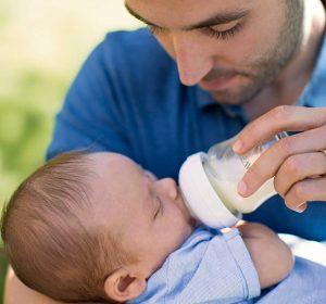 Papa donnant le biberon en verre à bébé